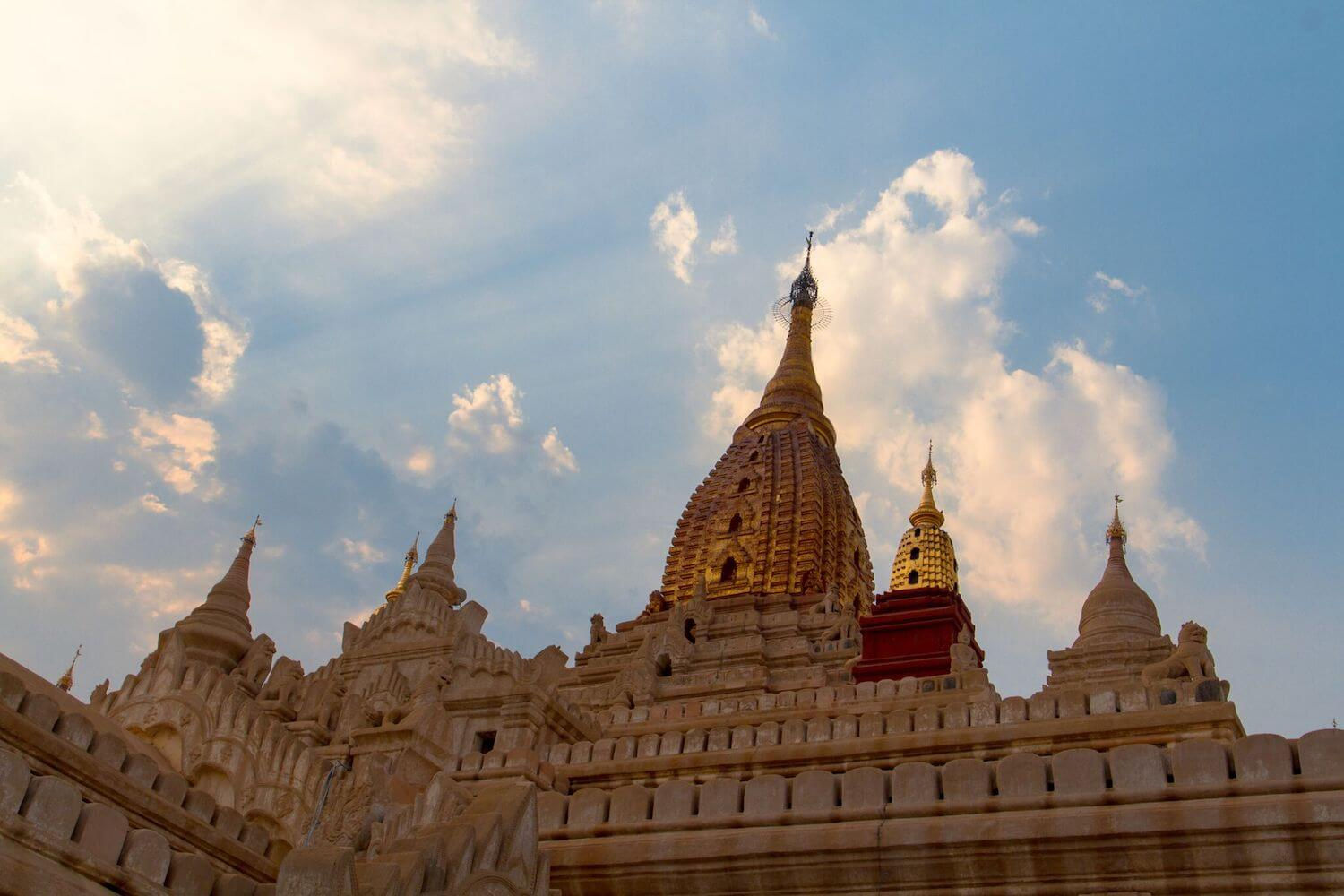 Best Myanmar Itinerary: Photo of a temple in Bagan Myanmar topped with gold and made of white stone shining in the sunlight. Photo taken by Ryan Brown of Lost Boy Memoirs, edited in Adobe Lightroom.