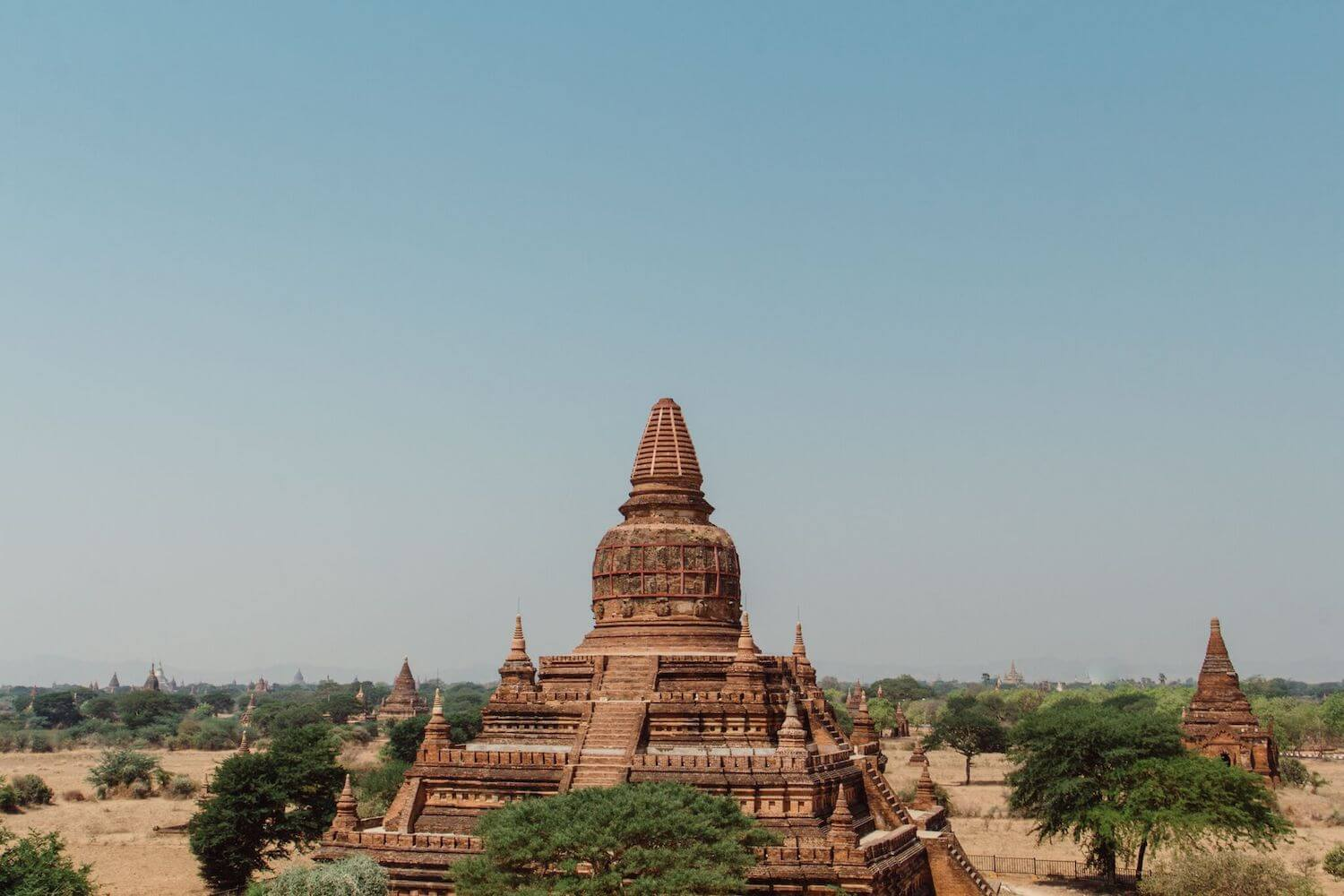 Best Myanmar Itinerary: Photo of an ancient red stone temple in Bagan Myanmar with many other temples in the distance. Photo taken by Ryan Brown of Lost Boy Memoirs, edited in Lightroom.