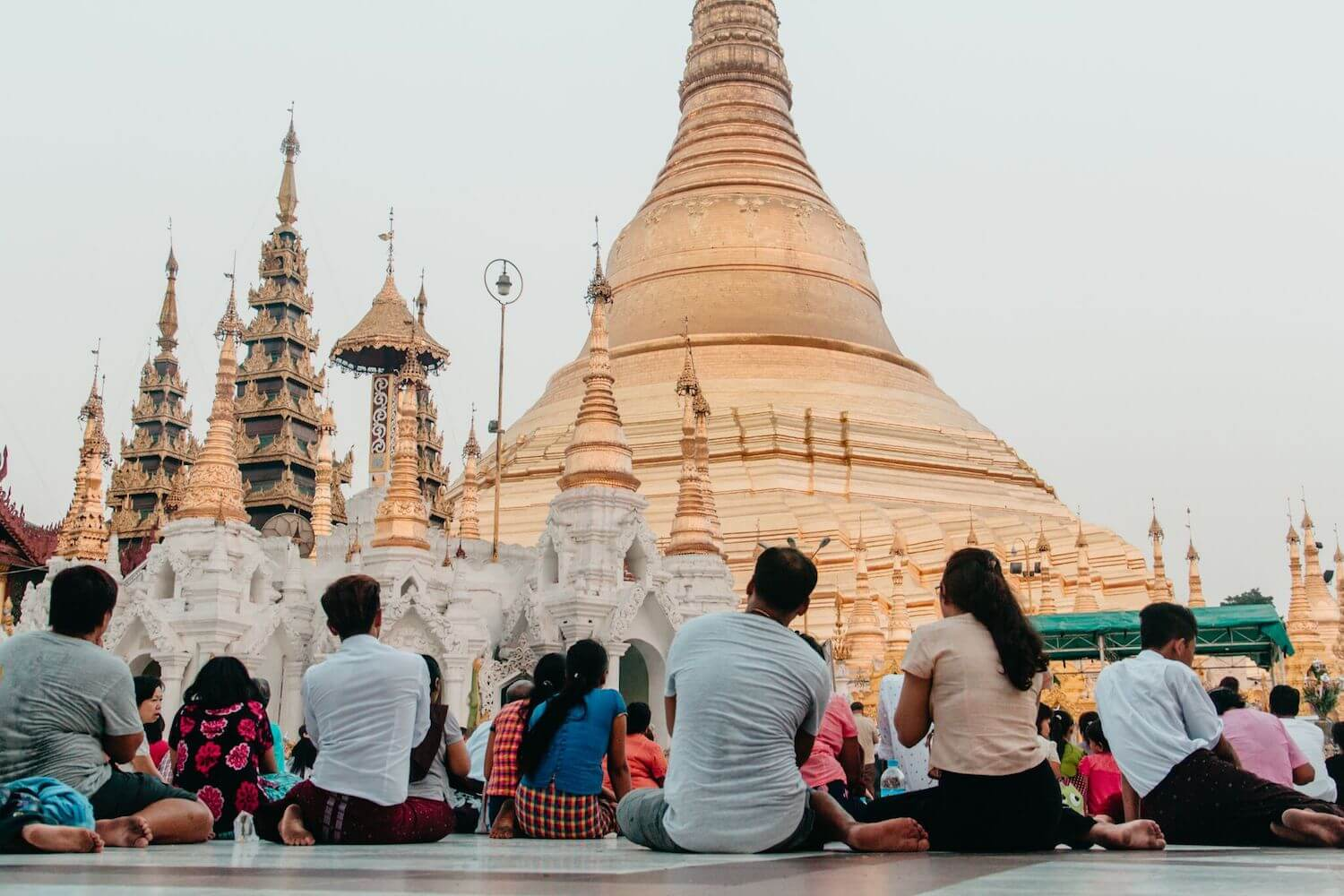 Best Myanmar Itinerary: Photo of Shwedagon Pagoda in Yangon Myanmar, the Golden Temple, with people sitting beneath the tallest spire at dusk. photo taken by Ryan Brown of Lost Boy Memoirs with Canon 650D Rebel T4i, edited in Lightroom.