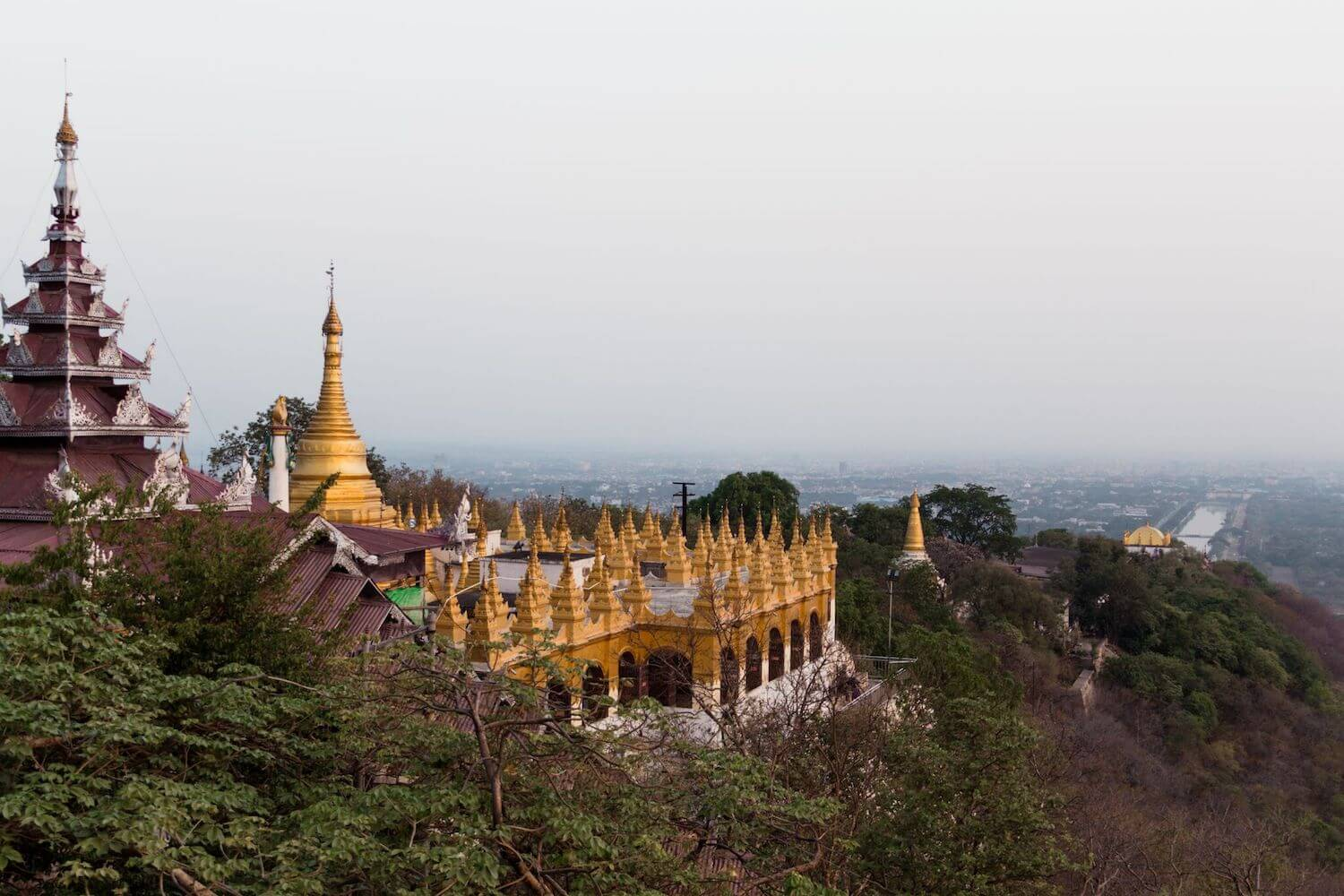 Best Myanmar Itinerary: Photo of the Mandalay Hill and Temple in Mandalay Myanmar, with the golden spires pointing over the trees atop the mountain overlooking Mandalay. Photo taken by Ryan Brown of Lost Boy Memoirs, edited in Lightroom.