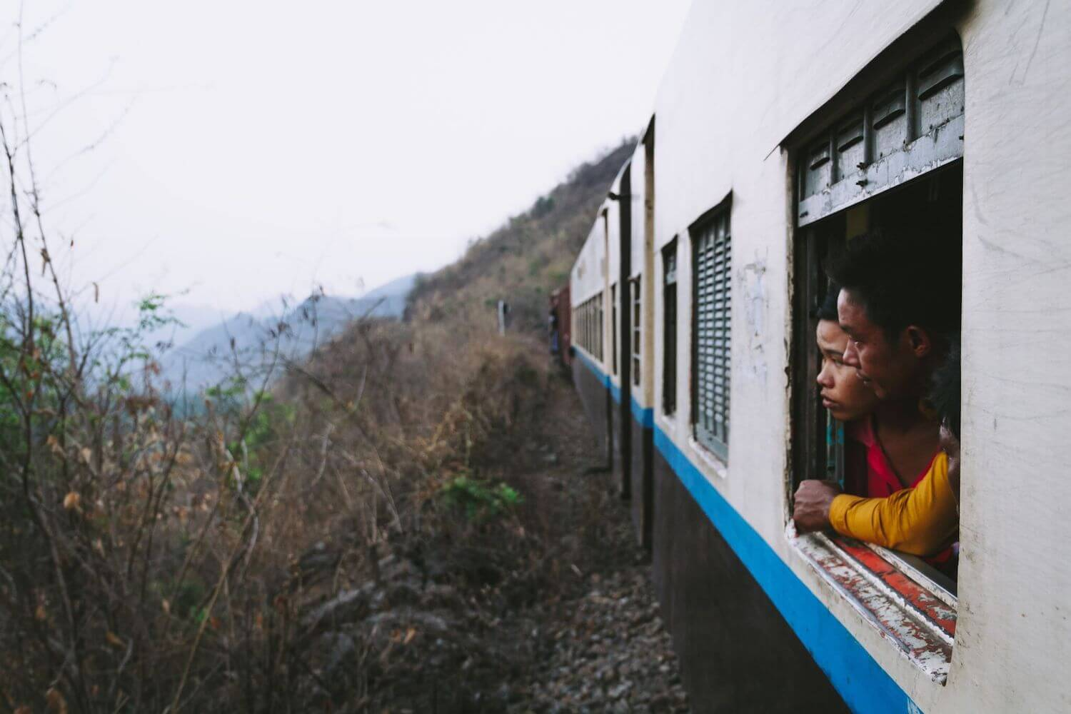 Best Myanmar Itinerary: Photo of two Myanmar people looking out of the old train window from Mandalay to Hsipaw down into the valley from the Goteik Viaduct. Photo by Ryan Brown of Lost Boy Memoirs, edited in Lightroom.
