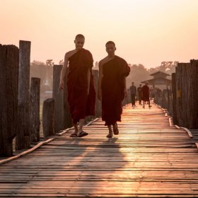 Photo of two monks in crimson robes walking along U Bein Bridge in Mandalay Myanmar at sunrise. Photo taken by Ryan Brown of Lost Boy Memoirs, edited in Lightroom.