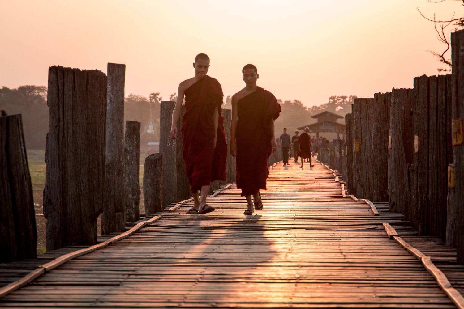 Best Myanmar Itinerary: Photo of two monks in crimson robes walking along U Bein Bridge in Mandalay Myanmar at sunrise. Photo taken by Ryan Brown of Lost Boy Memoirs, edited in Lightroom.