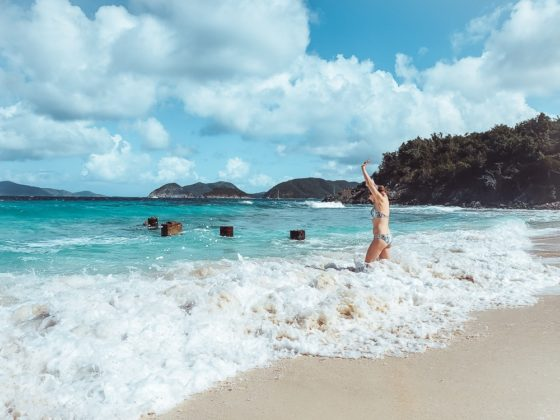 girl splashing in the waves at Denis Bay - St John underrated beaches